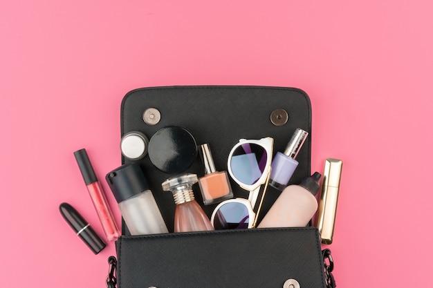 Bolsa pequena feminina cheia de produtos cosméticos