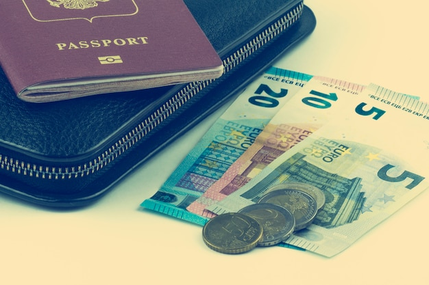 Bolsa preta grande e um passaporte vermelho.