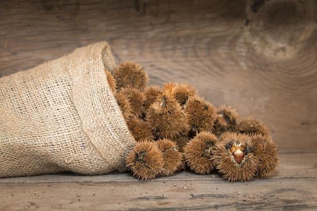 Bolsa que derrama castanhas na madeira rústica