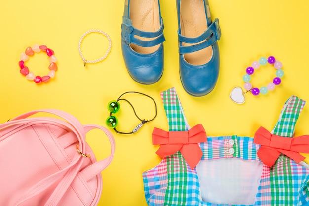 Bolsa rosa com vestido colorido, argola, presilhas e sapatos