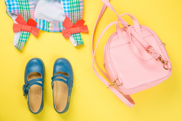 Bolsa rosa com vestido colorido e sapatos