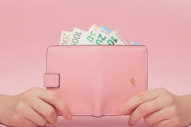 Bolsa rosa e notas de euro nas mãos femininas no fundo rosa. conceito de negócio e instagram.