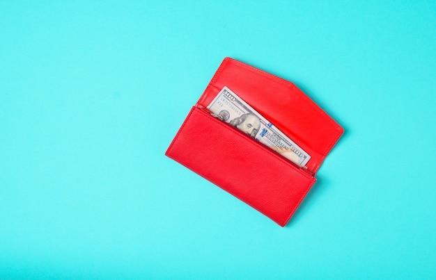 Bolsa vermelha com cem notas de dólar em um fundo azul pastel. vista do topo.