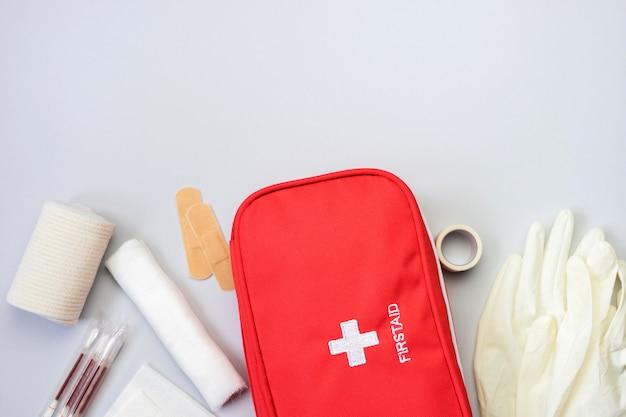 Bolsa vermelha de kit de primeiros socorros com equipamento médico e medicamentos para tratamento de trauma e lesões. vista superior plana leigos em fundo cinza. copie o espaço.