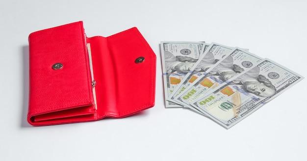 Bolsa vermelha e notas de cem dólares em branco.