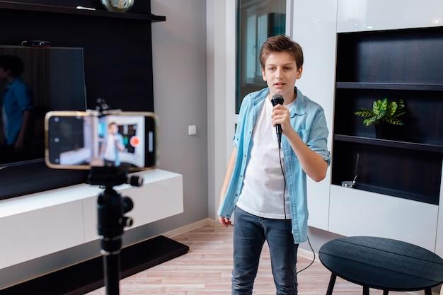 Bom blogueiro adolescente cantando em casa ao microfone.