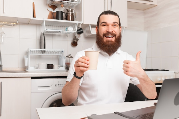 Bom café da manhã, homem feliz aparecendo o polegar e segurando uma xícara de café na cozinha