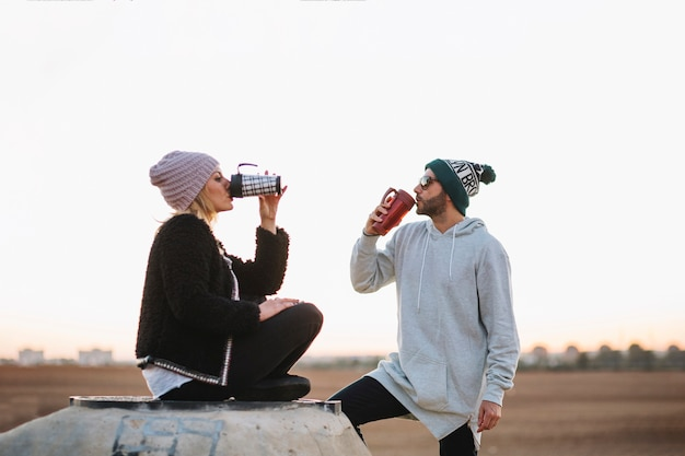 Bom casal bebendo na natureza