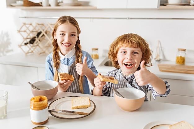 Bom começo. irmãos animados, adoráveis e entusiasmados, pensando que sanduíches de manteiga de amendoim são deliciosos, e estão animados para o dia enquanto saboreiam sua refeição matinal