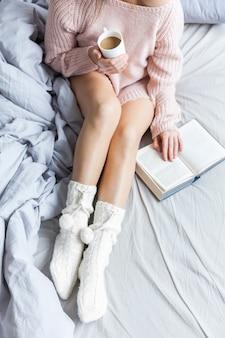 Bom dia com café. jovem mulher na cama com copo
