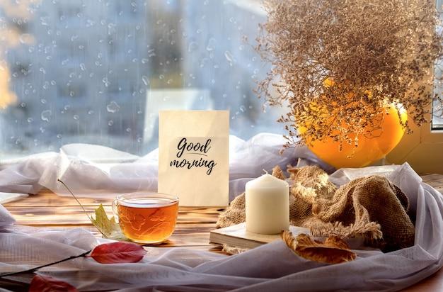 Bom dia! copo na janela antes da janela de gota de chuva de outono