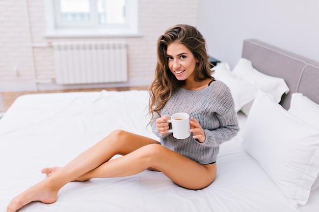 Bom dia de feliz menina bonita com longos cabelos castanhos relaxando no apartamento moderno. mulher jovem alegre com pernas longas nuas, no suéter cinza de malha com uma xícara de chá na cama branca.
