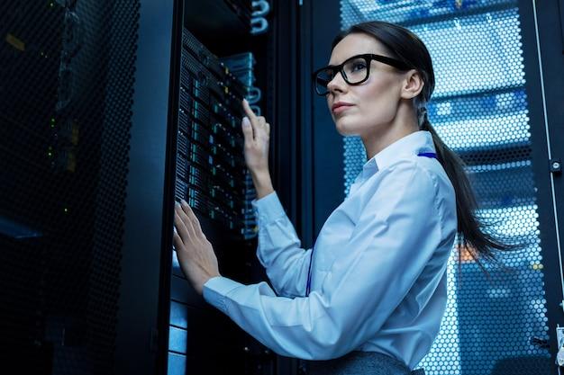 Bom dia de trabalho. mulher bonita determinada trabalhando com equipamento de servidor e usando óculos