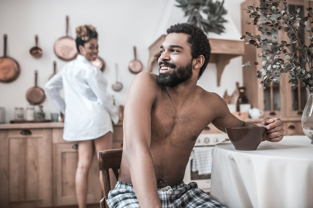 Bom dia, dia de folga. jovem sorridente e barbudo homem de pele escura comendo à mesa virando a cabeça para sua esposa cozinhando nos fundos da cozinha pela manhã