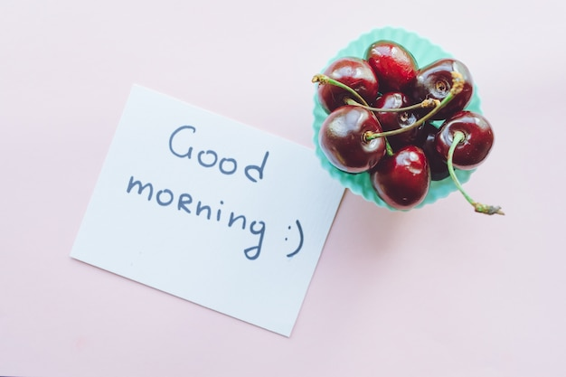 Bom dia. doce de cereja em rosa. cereja doce madura close-up.