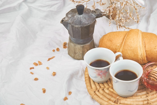 Bom dia. duas xícara de café com croissant e geléia.