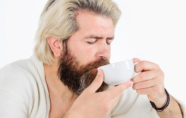 Bom dia. homem barbudo com uma xícara de café. bonito homem apreciando a caneca de bebida.