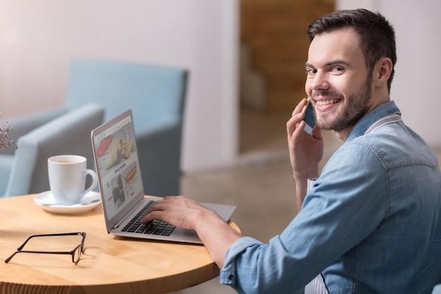 Bom dia. homem jovem bonito feliz rindo e falando no celular enquanto trabalhava no laptop.