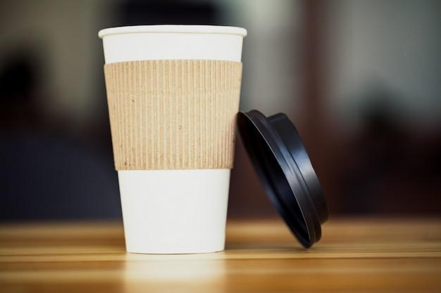 Bom dia. hora do café. café para viagem e feijão em uma mesa de madeira
