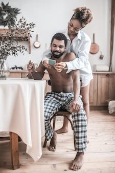 Bom dia. jovem barbudo marido de pele escura sem camisa tomando café da manhã na mesa e a esposa mostrando a tela do smartphone pela manhã na cozinha