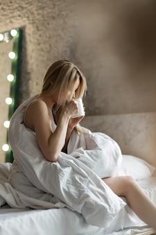 Bom dia meninas a loira com uma xícara de chá café café da manhã na cama acabei de acordar