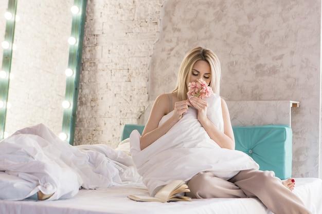 Bom dia meninas uma loira em um cobertor sentada na cama acordando de um sonho acaba de acordar
