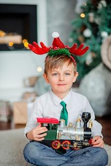Bom dia. menino feliz com um presente, trem de brinquedo, debaixo da árvore de natal. hora de realizar desejos.