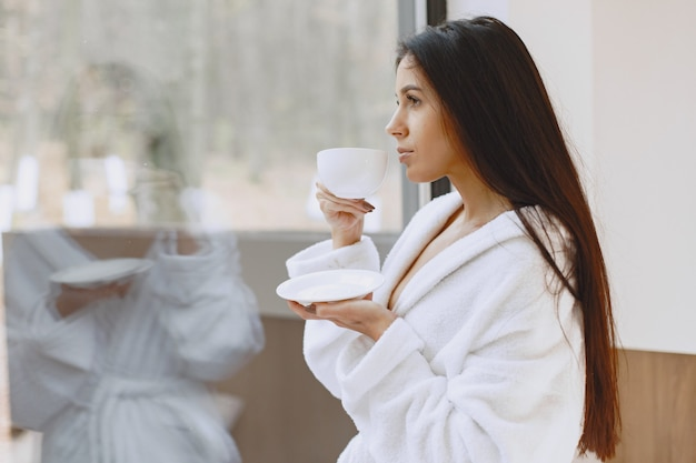 Bom dia. mulher bebe café. senhora perto da janela.