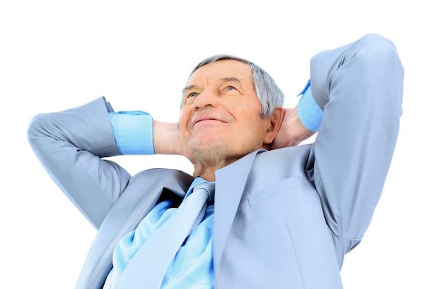 Bom empresário na idade, braços cruzados atrás da cabeça. isolado em um fundo branco.