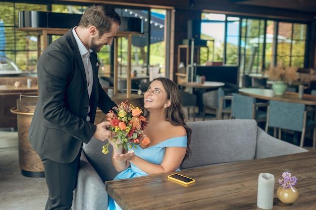 Bom encontro. homem carinhoso e amoroso sorridente, terno com flores e mulher feliz sentada no café