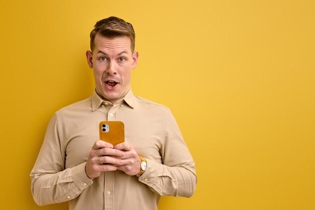 Bom homem europeu segurando um smartphone nas mãos, criando um influenciador de estratégia social, pensando