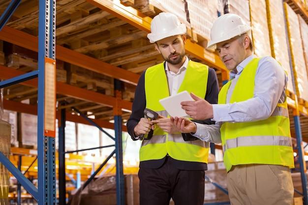 Bom homem inteligente olhando para o tablet enquanto discute nuances de trabalho com seu chefe