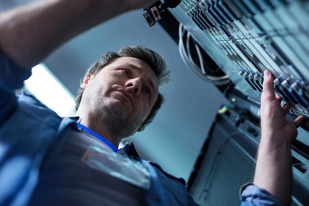 Bom homem sério e agradável em frente ao servidor de dados e olhando para ele enquanto trabalha no data center