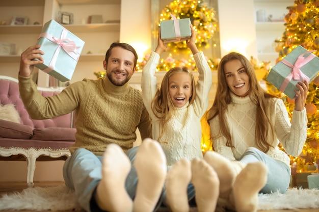 Bom humor. família adorável sentada no chão e se sentindo festiva