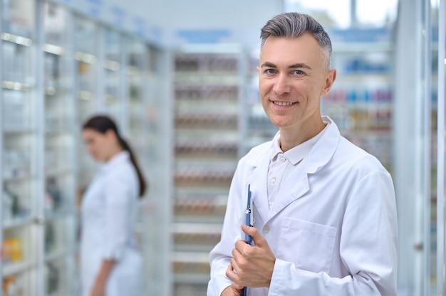 Bom humor. farmacêutico adulto jovem sorridente com uma pasta e uma funcionária de cabelos compridos atrás, em pé no corredor da farmácia