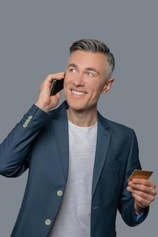 Bom humor. homem maduro feliz com cartão de crédito falando no smartphone, olhando alegremente para cima e para o lado na foto do estúdio