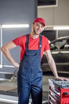 Bom humor. jovem adulto atraente e sorridente, vestindo roupas de trabalho em pé, posando na oficina mecânica
