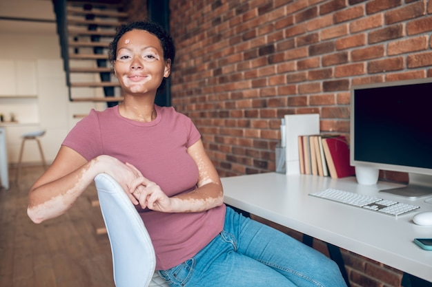 Bom humor. jovem afro-americana sentada à mesa em seu local de trabalho e sorrindo