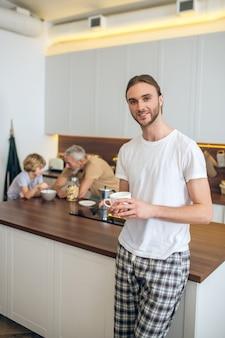 Bom humor. jovem de camiseta branca em pé na cozinha e sorrindo lindamente