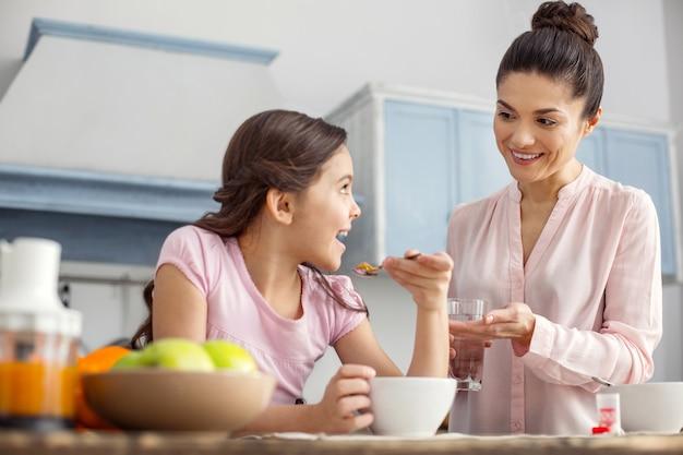 Bom humor. jovem mãe de cabelos escuros muito feliz sorrindo e dando vitaminas para sua filha e a menina tomando café da manhã e sentadas na casa de t