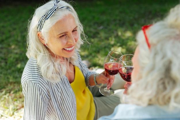 Bom humor. mulher idosa feliz sorrindo enquanto bebe vinho junto com o marido