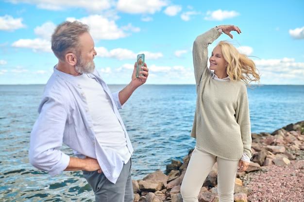 Bom humor. perfil de homem adulto envolvido com smartphone tirando fotos de uma mulher bonita com o vento no cabelo em pé na praia