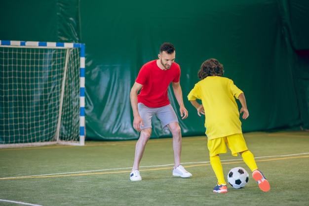 Bom jogo. menino de uniforme amarelo jogando futebol com o treinador e parecendo envolvido