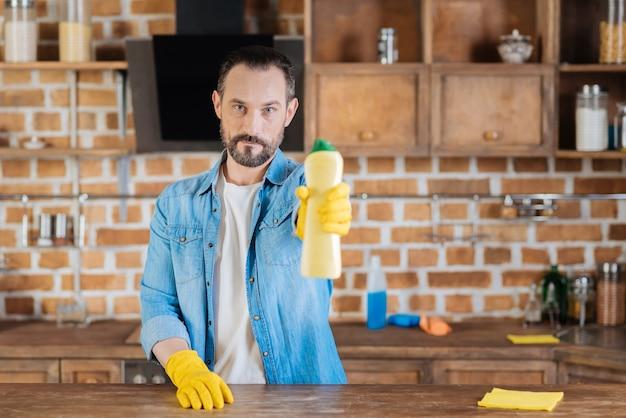 Bom limpador atraente masculino mostrando limpador em pé e olhando para a câmera