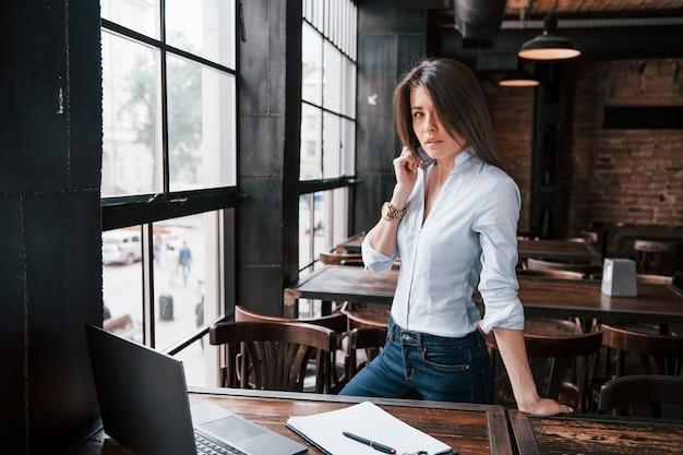 Bom lugar para trabalhar. mulher de negócios com roupas oficiais está dentro de casa no café durante o dia.