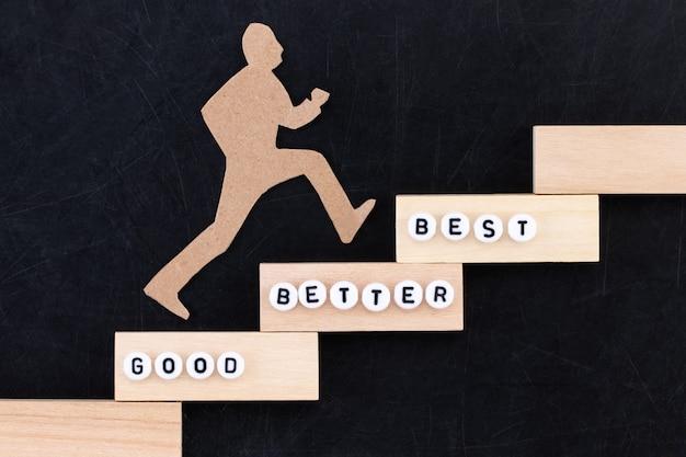 Bom - melhor - melhor homem de papel subindo os degraus para o sucesso