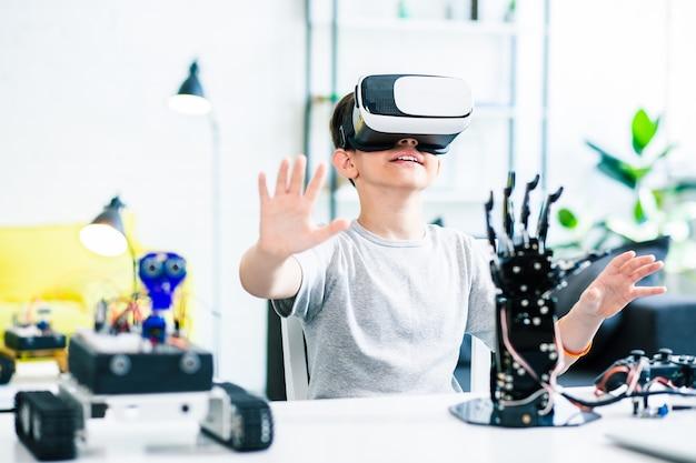 Bom menino inteligente e entusiasmado sentado à mesa e usando óculos de realidade virtual enquanto faz experiências com seus dispositivos robóticos