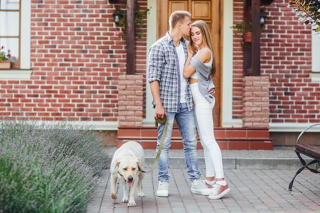 Bom momento! jovem casal em frente a casa grande com um lindo labrador