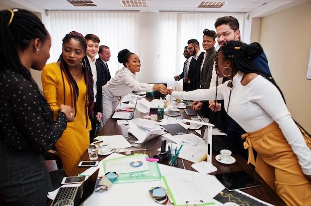 Bom negócio. equipe de negócios multirraciais, abordando a reunião em torno da mesa da sala de reuniões e apertando as mãos.