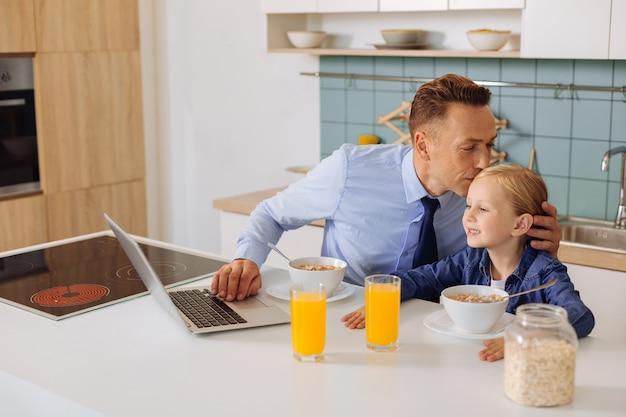 Bom pai sentado junto com sua filha e beijando-a enquanto expressa seus sentimentos